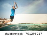 boy in swimwear makes a jump in ... | Shutterstock . vector #701295217
