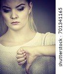 Small photo of Unlike, dislike, failure gestures concept. Sad woman showing thumb down gesture, studio shot grey background.