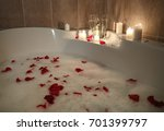 Stock photo glasses of alcoholic drink with candles on bathtub filled with foam and rose petals 701399797