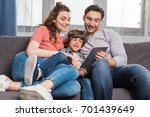 happy family using tablet while ... | Shutterstock . vector #701439649