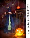 Small photo of Portrait of a cute little girl in witch costume scares somebody. Halloween holidays.