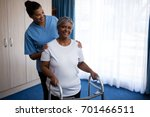nurse assisting senior woman in ... | Shutterstock . vector #701466511