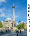 Small photo of LONDON, UK - MAY 23, 2017: View of a fountain and the Nelson's Column in Trafalgar Square in London on a sunny spring day. Tourists walking and sitting all over the place. Police on patrol.