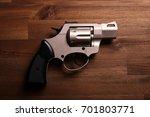 revolver handgun on wood floor | Shutterstock . vector #701803771