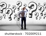 Small photo of View of a Businessman in front of a wall trying to find find answers - Daily life concept