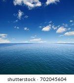 blue sea water surface on sky | Shutterstock . vector #702045604