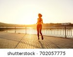 rear view of girl running on... | Shutterstock . vector #702057775