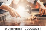 hand of man take cooking of... | Shutterstock . vector #702060364