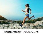 trail runner woman running at... | Shutterstock . vector #702077275