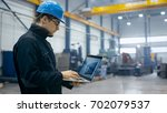 factory worker in a hard hat is ... | Shutterstock . vector #702079537