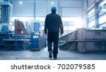 factory worker in a hard hat is ... | Shutterstock . vector #702079585