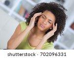 lady massaging her temples | Shutterstock . vector #702096331
