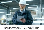 senior engineer in hardhat is... | Shutterstock . vector #702098485