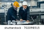 two engineers discuss a... | Shutterstock . vector #702098515
