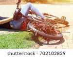 a woman fell with her bicycle... | Shutterstock . vector #702102829