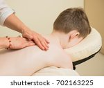 therapist making back massage... | Shutterstock . vector #702163225