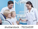 Dentist gives the child a toothbrush in the dental office - stock photo