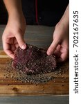 Small photo of Cooking raw meat with pepper and spices marinade on wooden table background by chef hands.