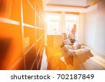 woman unpacking lamp from... | Shutterstock . vector #702187849