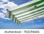 green and white striped awning...   Shutterstock . vector #702196681