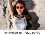 woman in red sunglasses lies on ... | Shutterstock . vector #702210799