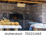 old stone oven and breads | Shutterstock . vector #702211465