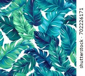 turquoise and green tropical leaves. Seamless graphic design with amazing palms. Fashion, interior, wrapping, packaging suitable. Realistic palm leaves. | Shutterstock vector #702226171