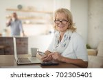 portrait of senior woman using... | Shutterstock . vector #702305401