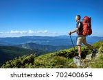hiking in the mountains with a... | Shutterstock . vector #702400654