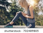 knee injury  woman runner with... | Shutterstock . vector #702489805