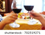 two young women drinking wine... | Shutterstock . vector #702519271