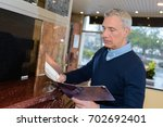 man choosing marble in a modern ... | Shutterstock . vector #702692401