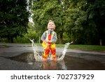 child in a yellow waterproof... | Shutterstock . vector #702737929