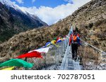 Small photo of Active man backpacker crossing suspension bridge with buddhist prayer flags on the Langtang trek in Nepal.