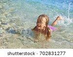 child blond girl enjoying ocean ... | Shutterstock . vector #702831277