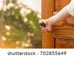 women hand open door knob or...   Shutterstock . vector #702855649