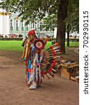 Small photo of August 12, 2017 in the city of St. Petersburg in the Palace Square performance of a street musician in the costume of an American Indian