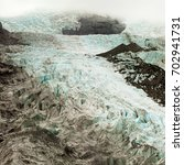 Small photo of Large alpine glacier icefield partly hidden in clouds melting rapidly due to global warming on a steep slope icefall forming a maze of deep crevasses