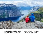 couple sits on rock and looks... | Shutterstock . vector #702947389