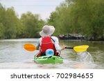 girl in green kayak kayaking in ... | Shutterstock . vector #702984655