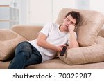 Young man asleep in front of TV set on sofa at home - stock photo