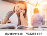 bored girl studying at table... | Shutterstock . vector #703255699