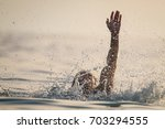 man drowns in the sea | Shutterstock . vector #703294555