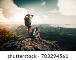 two hikers relax on top of a... | Shutterstock . vector #703294561