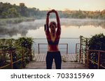 girl runner on a warm up before ... | Shutterstock . vector #703315969