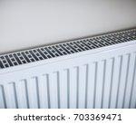 white radiator in an apartment. ... | Shutterstock . vector #703369471