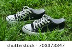 black and white sneakers on the ... | Shutterstock . vector #703373347