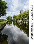Small photo of Galway, Ireland - August 3, 2017: Corrib River arm is channeled between walls in park over which Saint Vincents Convent of Mercy towers show. Cloudscape and lots of green.