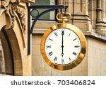 a clock face on town building | Shutterstock . vector #703406824