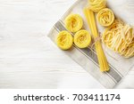 raw pasta on the white wooden... | Shutterstock . vector #703411174